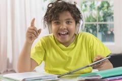 Il ragazzo sta facendo il compito e la musica d'ascolto fotografia stock libera da diritti