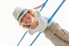 Il ragazzo sta facendo la ginnastica su un palo rampicante immagine stock libera da diritti