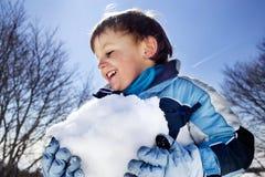 Il ragazzo sta facendo una grande palla di neve nelle montagne, divertimento dell'inverno Fotografie Stock Libere da Diritti
