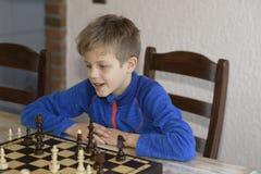 Il ragazzo sta giocando gli scacchi fotografia stock