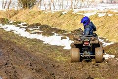 Il ragazzo sta guidando un ATV fuori strada fotografia stock