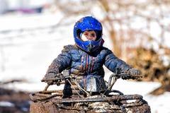 Il ragazzo sta guidando un ATV fuori strada immagine stock