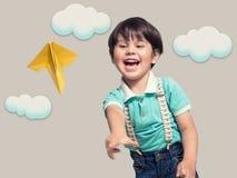 Il ragazzo sta lanciando un aereo di carta immagini stock libere da diritti
