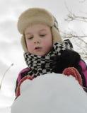 Il ragazzo sta lavorando diligente scolpisce un pupazzo di neve Immagini Stock Libere da Diritti