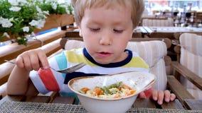 Il ragazzo sta mangiando la pasta Nutrizione adeguata Un bambino affamato stock footage