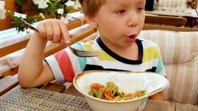 Il ragazzo sta mangiando la pasta Nutrizione adeguata Un bambino affamato video d archivio