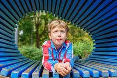 Il ragazzo sta rilassandosi sul campo da giuoco durante l'estate Bambino che fa i fronti divertenti fotografia stock