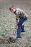 Il ragazzo sta scavando la terra in autunno del parco Persona che scava nel giardino fotografia stock libera da diritti