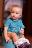 Il ragazzo sta sedendosi sul chamberpot Fotografia Stock Libera da Diritti