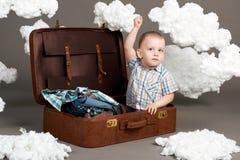 Il ragazzo sta sedendosi in una valigia e sta andando in viaggio, nuvole di ovatta come decorazione, fondo grigio fotografia stock libera da diritti
