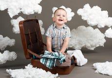 Il ragazzo sta sedendosi in una valigia e sta andando in viaggio, nuvole di ovatta come decorazione, fondo grigio immagini stock libere da diritti