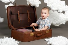 Il ragazzo sta sedendosi in una valigia e sta andando in viaggio, nuvole di ovatta come decorazione, fondo grigio fotografia stock