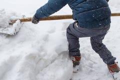 Il ragazzo sta spalando la neve Immagine Stock