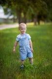 Il ragazzo sta su erba Fotografia Stock