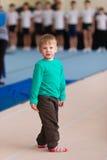 Il ragazzo sta sul tappeto relativo alla ginnastica nella palestra Immagine Stock Libera da Diritti