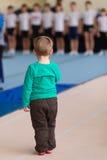 Il ragazzo sta sul tappeto relativo alla ginnastica nella palestra Immagine Stock