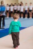Il ragazzo sta sul tappeto relativo alla ginnastica nella palestra Immagini Stock