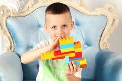 Il ragazzo sta tenendo un giocattolo in sua mano immagini stock libere da diritti