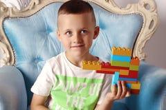 Il ragazzo sta tenendo un giocattolo in sua mano immagini stock