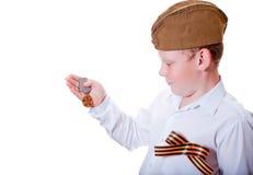 Il ragazzo sta tenendo una medaglia Immagini Stock