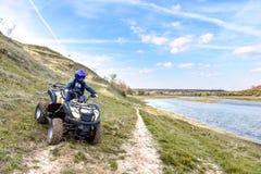 Il ragazzo sta viaggiando su un ATV Bella vista immagine stock