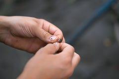 Il ragazzo su pesca copre l'esca sulle canne da pesca dei ganci Fotografia Stock Libera da Diritti