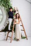 Il ragazzo sulle scale della costruzione e sulla ragazza che lo sostengono Fotografia Stock Libera da Diritti