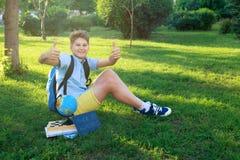 Il ragazzo sveglio, astuto, giovane in camicia blu si siede sull'erba con il globo, i libri di esercizi, lavagna e tiene i suoi p immagine stock