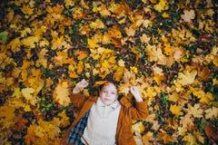 Il ragazzo sveglio cammina e posa in un parco variopinto di autunno fotografia stock libera da diritti