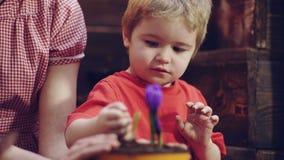 Il ragazzo sveglio del bambino aiuta sua madre a preoccuparsi per le piante Madre ed suo figlio impegnati nel giardinaggio nel co archivi video