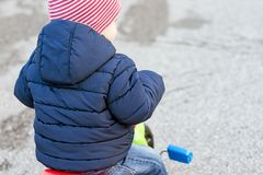 Il ragazzo sveglio del bambino in vestiti autunnali caldi ha girato da dietro divertiresi con il triciclo immagini stock libere da diritti