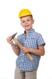 Il ragazzo sveglio dell'adolescente in camicia a quadretti blu e un casco della costruzione con il martello su bianco hanno isola Immagine Stock Libera da Diritti