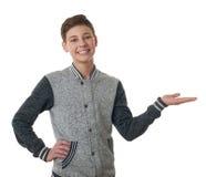 Il ragazzo sveglio dell'adolescente in maglione grigio sopra bianco ha isolato il fondo Fotografia Stock