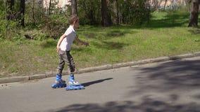 Il ragazzo sveglio guida sui pattini di rullo in parco archivi video