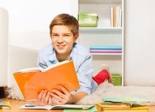 Il ragazzo sveglio ha letto un libro a casa sul pavimento Fotografia Stock Libera da Diritti