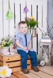 Il ragazzo sveglio in jeans è adatta alla seduta su un fondo luminoso succoso Immagini Stock