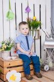 Il ragazzo sveglio in jeans è adatta alla seduta su un fondo luminoso succoso Fotografie Stock Libere da Diritti