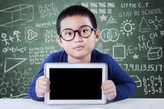 Il ragazzo sveglio mostra lo schermo della compressa nella classe Fotografie Stock Libere da Diritti