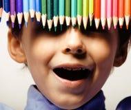 Il ragazzo sveglio piccolo con le matite di colore si chiude sul sorridere, fronte di istruzione colorato fotografie stock