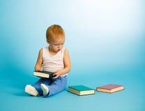 Il ragazzo sveglio sceglie che cosa leggere da tre libri fotografia stock