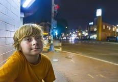 Il ragazzo sveglio sorride stanco mentre si siede fuori di notte Fotografia Stock