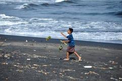 Il ragazzo sveglio sta giocando sulla spiaggia di Sanur fotografia stock