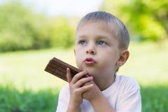 Il ragazzo sveglio sta mangiando una barra di cioccolato Immagine Stock