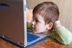 Il ragazzo sveglio sta spingendo i computer portatili tastiera e sta esaminando lo schermo Immagini Stock Libere da Diritti