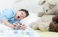 Il ragazzo sveglio sveglia e sbadigliando fotografia stock