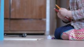 Il ragazzo sveglio in vetri divertenti disegna con entrambe le mani su carta a casa stock footage