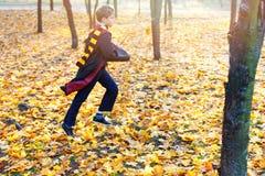 Il ragazzo sveglio in vetri sta nel parco di autunno con le foglie dell'oro, tiene il libro in sue mani, immagini stock libere da diritti