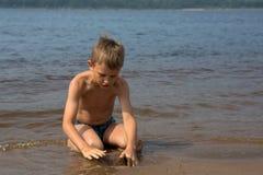 Il ragazzo sviluppa le figure dalla sabbia sulla spiaggia fotografia stock libera da diritti
