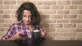Il ragazzo teenager affamato mangia nella cucina ed utilizza uno smartphone stock footage