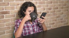 Il ragazzo teenager affamato mangia nella cucina ed utilizza uno smartphone video d archivio